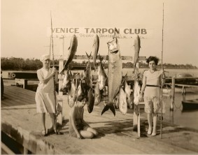 Venice Tarpon Club women on a dock, next to a display of fish